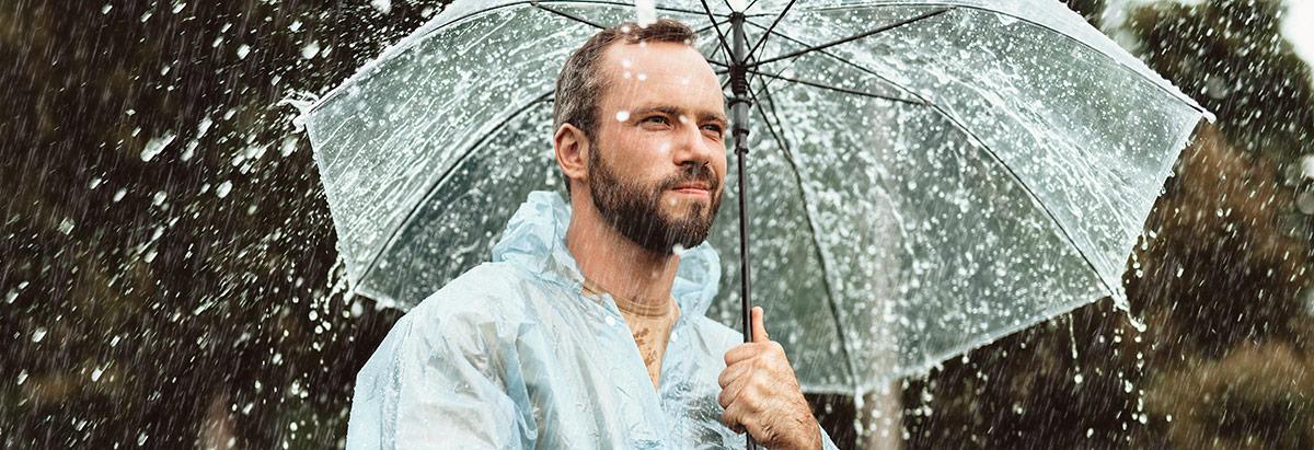 Mann mit Regenschirm im Regen
